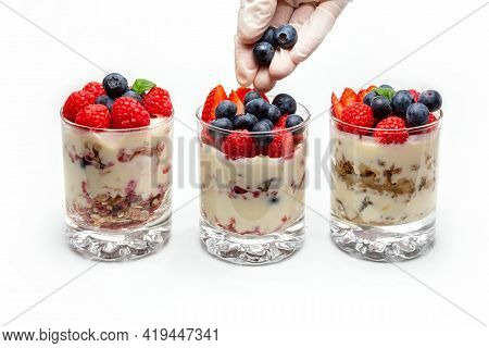 Muesli With Yogurt And Berries In A Glass On A White Background. The Chefs Hand Puts Blueberry Into