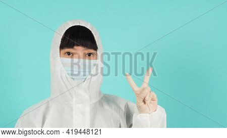 Asian Woman Wear Face Mask And Ppe Suit Doing Victory Hand Or Peace Sign On Mint Green Or Tiffany Bl