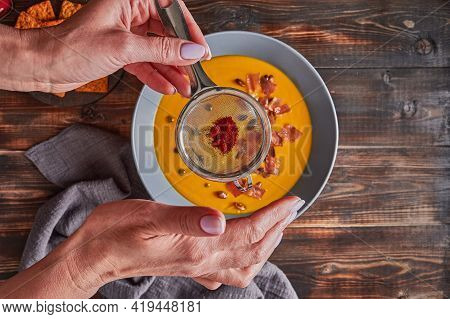 Womans Hands Sprinkled With Sieve Paprika On Traditional Pumpkin Puree Cream Soup With Carrots, Onio
