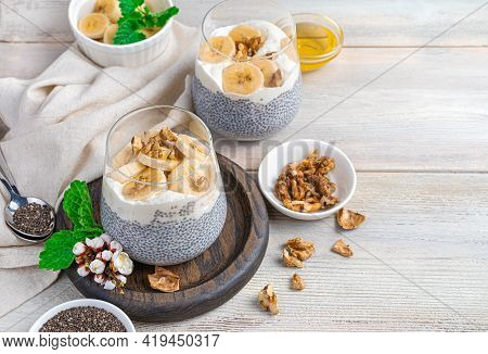 Chia Pudding With Banana, Nuts And Honey On A Beige Background With Space To Copy.