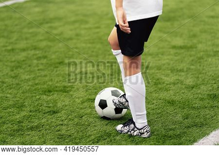 Soccer Player With White And Black Football Ball. Young Athlete Kicking Ball On Grass Field. Boy In