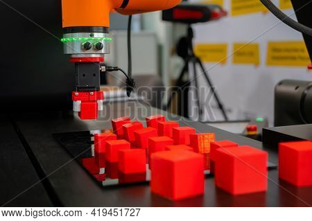 Pick And Place Robotic Clamp Arm Manipulator Moving Red Toy Blocks At Modern Robot Trade Show, Exhib