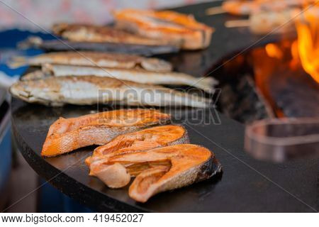 Process Of Grilling Salmon Steaks And Mackerel Fish On Black Brazier At Summer Local Food Market - C