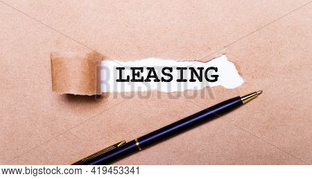 Torn Kraft Paper, White Background With The Text Leasing. Nearby Is A Black Handle. View From Above
