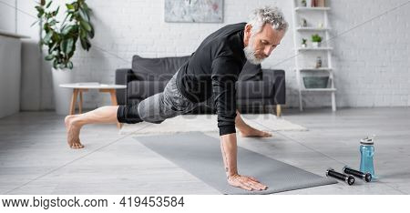 Barefoot Man With Grey Hair Working Out On Fitness Mat Near Dumbbells In Living Room, Banner.