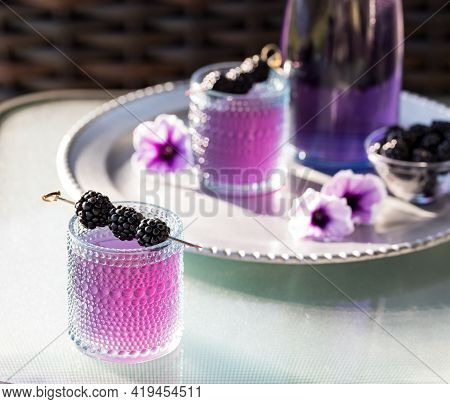 Blackberry Mocktail With Blackberry Skewer And A Tray Of The Same In Soft Focus In Behind.