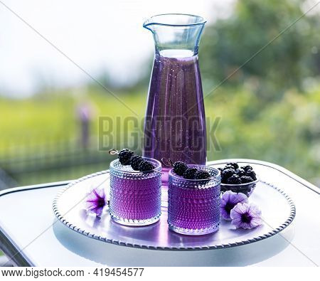 Two Glasses Of Blackberry Mocktail Served On A Metal Tray Garnished With Blackberry Skewers.