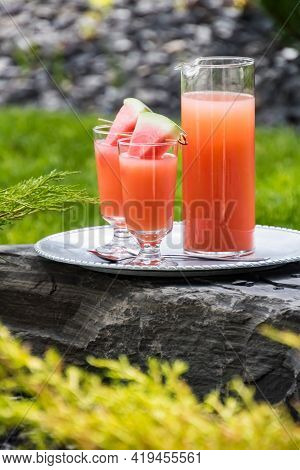Guava Juice Garnished With Watermelon Wedges On A Metal Tray Resting On A Rock Outside.