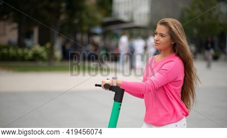Woman driving scooter in a city, urban mobility and sustainable ecologic transportation concept