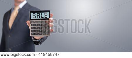 Word Sale On Calculator Screen. Businessman Shows Calculator With Word Sale On Screen. Business And