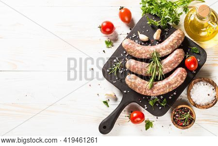 Bratwurst Or Sausages On Cutting Board At White Wooden Table Table.