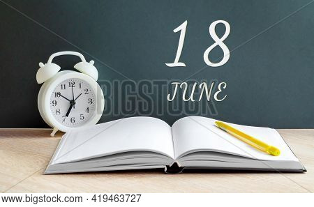 June 18. 18-th Day Of The Month, Calendar Date.a White Alarm Clock, An Open Notebook With Blank Page