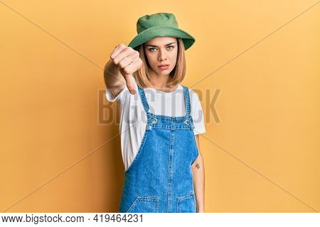 Young caucasian blonde woman wearing denim jumpsuit and hat with 90s style looking unhappy and angry showing rejection and negative with thumbs down gesture. bad expression.