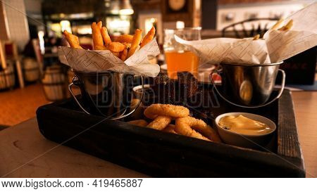 Beer Set Of Snacks On A Wooden Tray. Onion Rings, Cheese Sticks, French Fries In A Bucket. Sauces. S