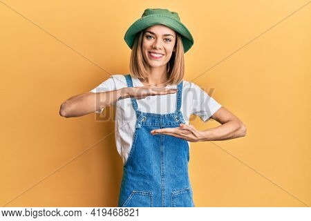 Young caucasian blonde woman wearing denim jumpsuit and hat with 90s style gesturing with hands showing big and large size sign, measure symbol. smiling looking at the camera. measuring concept.