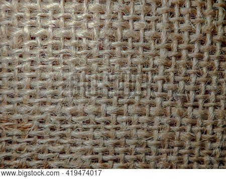 Light Brown Beige Linen Texture, Burlap Fabric As Background. Close Up Beige Weaving Or Mesh Fabric