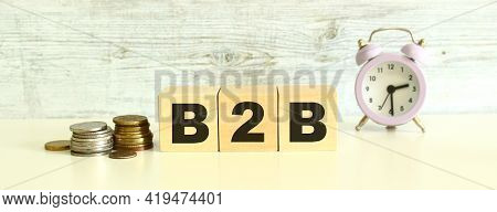 There Are Three Wooden Cubes With Letters On The Table Next To The Coins. The Word B2b. On A Gray Ba