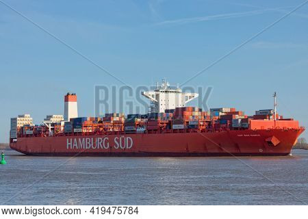 Stade, Germany – April 16, 2021: Reefer container ship CAP SAN MARCO, operated by shipping company  HAMBURG SÜD, heading to Hamburg on Elbe river