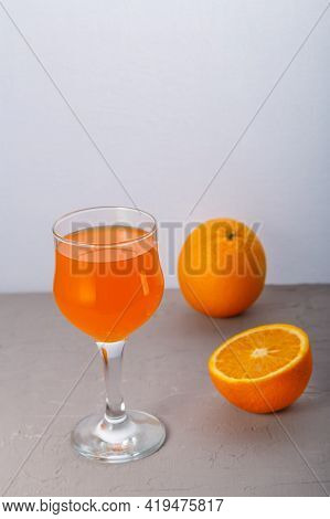 Orange Juice In A Glass Near Oranges On A Gray Background. Vertical Photo