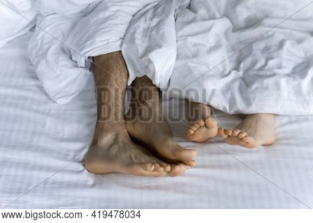 Morning And Waking Up. Feet Under The Covers In Bed In The Morning. Women's Feet Under The Covers In