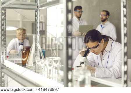 Focus On Woman Wearing Safety Goggles And Lab Coat Working With Microscope