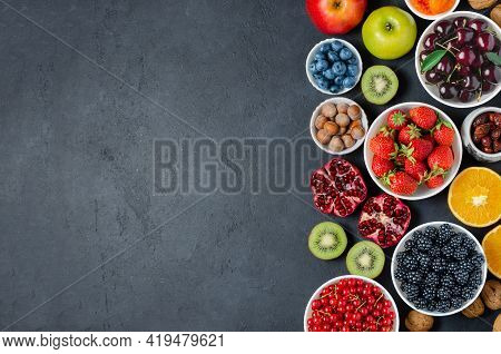Food With A High Content Of Antioxidants: Berries, Nuts, Fruits. Black Concrete Background. Copy Spa
