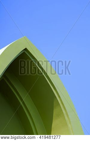 Low Angle View Of Vintage Green Gable Roof In Curved Triangle Shape Against Blue Sky Background In V