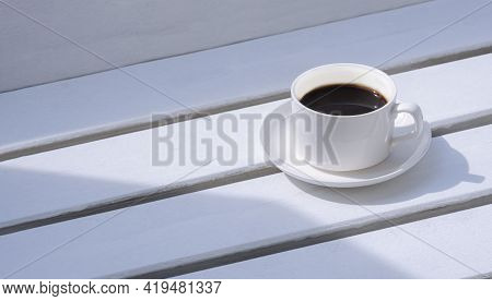 Morning Sunlight On Surface Of Black Coffee In White Ceramic Cup On White Wooden Garden Bench In Vin