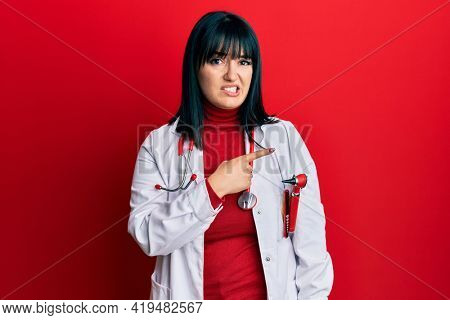 Young hispanic woman wearing doctor uniform and stethoscope pointing aside worried and nervous with forefinger, concerned and surprised expression