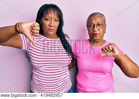 Hispanic family of mother and daughter hugging together with love with angry face, negative sign showing dislike with thumbs down, rejection concept