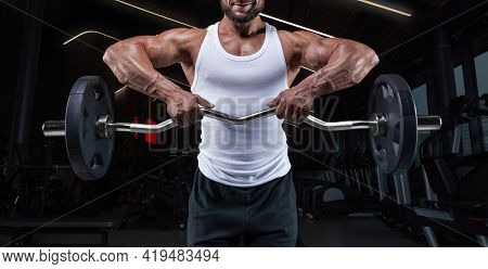 Handsome Young Man Working Out With A Barbell In The Gym. Shoulder Pumping. Barbell Pull To The Chin