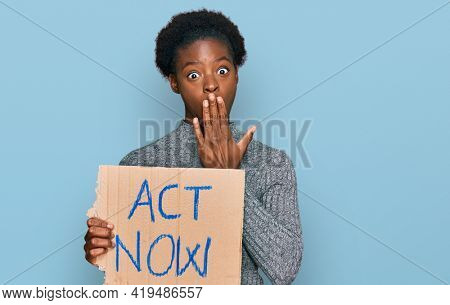 Young african american girl holding act now banner covering mouth with hand, shocked and afraid for mistake. surprised expression