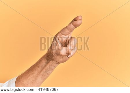 Senior caucasian hand over yellow isolated background gesturing fingers crossed, superstition and lucky gesture, lucky and hope expression