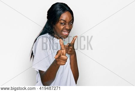 Young african american woman wearing casual white t shirt pointing fingers to camera with happy and funny face. good energy and vibes.