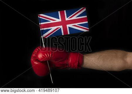 Boxer Hand Holds Flag Of Great Britain. Boxing Glove With The Great Britain Flag. Black Background
