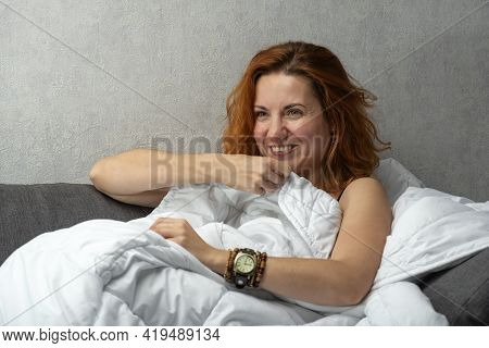 Red-haired Girl Smiles And Covered With White Blanket. Playful Gaze.