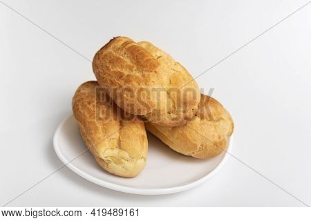 Profiteroles, Puffs, Popovers, Eclaires On White Saucer Against White Background.