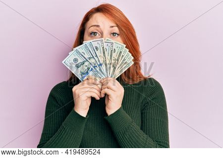 Beautiful redhead woman holding dollars close to face depressed and worry for distress, crying angry and afraid. sad expression.