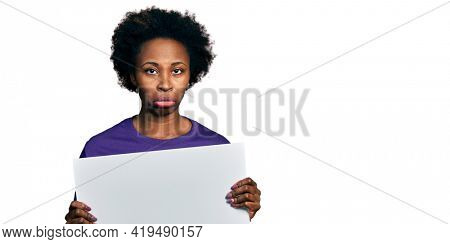 African american woman with afro hair holding blank empty banner depressed and worry for distress, crying angry and afraid. sad expression.