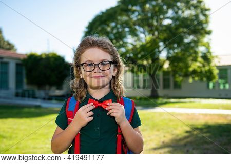Child With Rucksacks In The School Park. Pupils With Backpacks Outdoors. Nerd Pupil Ties A Bowtie, C