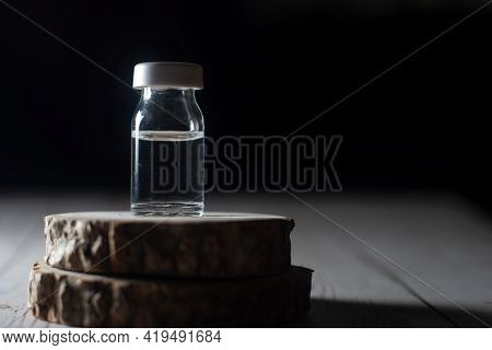Glass Vial On A Wooden Block Shot Against Black With Copyspace Showing Natural Medicine Antibiotic S