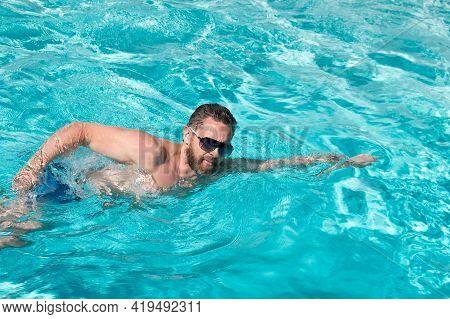 Summer Vacation. Man Swimming In Pool. Summertime Pool Resort. Active Weekend.