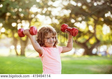 Boy Workout In Park. Kid Sport. Child Exercising With Dumbbells. Sporty Child With Dumbbell Outdoor.