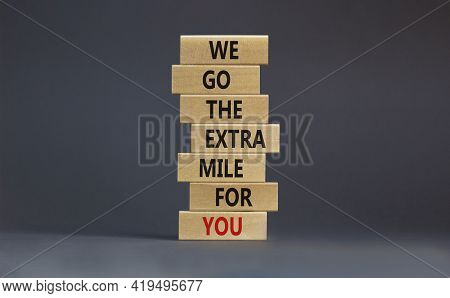 Go The Extra Mile Symbol. Wooden Blocks With Words 'we Go The Extra Mile For You'. Beautiful Grey Ba