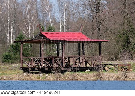 A Wooden Gazebo With A Red Roof Stands Near The Forest.