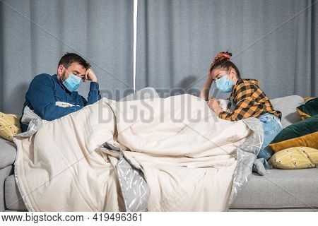 Young Couple Suffering From A Common Cold And Flu Sit At Home Wrapped In Blankets And Wipe Their Nos