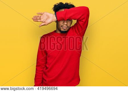 Young african american man with beard wearing casual winter sweater covering eyes with arm, looking serious and sad. sightless, hiding and rejection concept