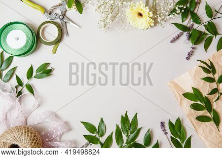 Branches With Leaves, Flowers And Florists Work Tools On A White Background. Flat Layout With Space