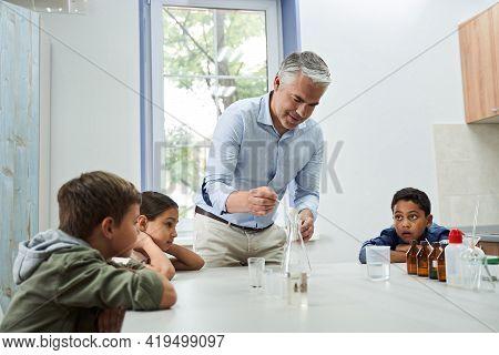 Waist Up Portrait Of The Handsome Grey Haired Teacher Teaches Chemistry