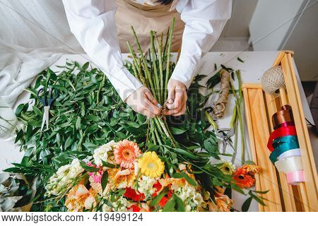 A Florist Ties A Bouquet Of Fresh Flowers With Twine On His Desk Littered With Cut Leaves. Top View